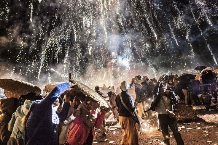 TAUNGGYI, MYANMAR 11/12/2016 People at a festival shielded themselves from fireworks that ignited prematurely and fell from a hot-air balloon. Ye Aung Thu/Agence France-Presse — Getty Images