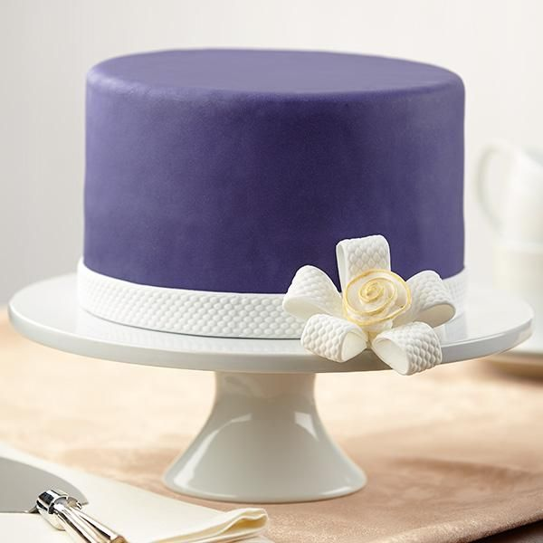 """""""Flower-Knotted Bow Cake""""   A smooth navy blue fondant cake is beautifully set off by a textured fondant flower bow and ribbon. Make it in black and add some cards and you have a perfect magic show themed cake. Plan a perfect party at http://idomagic.com/party-planning/"""