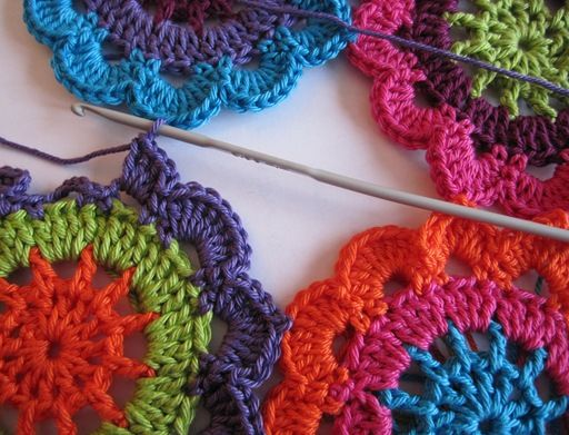 Interesting idea! She crochets a granny square into the space between the four circles.