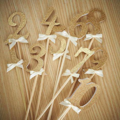Nuestro confeti Números de la tabla en los palillos son perfectas para agregar un poco chispa a tus centros de mesa boda, cumpleaños o aniversario. Se ven hermosas sobresale un arreglo floral.  Estas tabla números fueron diseñados usando oro fino brillo documento número (brillo en el reverso también) y adornado con un arco de cinta de Satén marfil lujo todos rematado en un taco de bambú.  Tamaño: Número de height(2.5) - longitud de la varilla - (13) Cantidad: Set de 5 o más  Haga clic aquí…