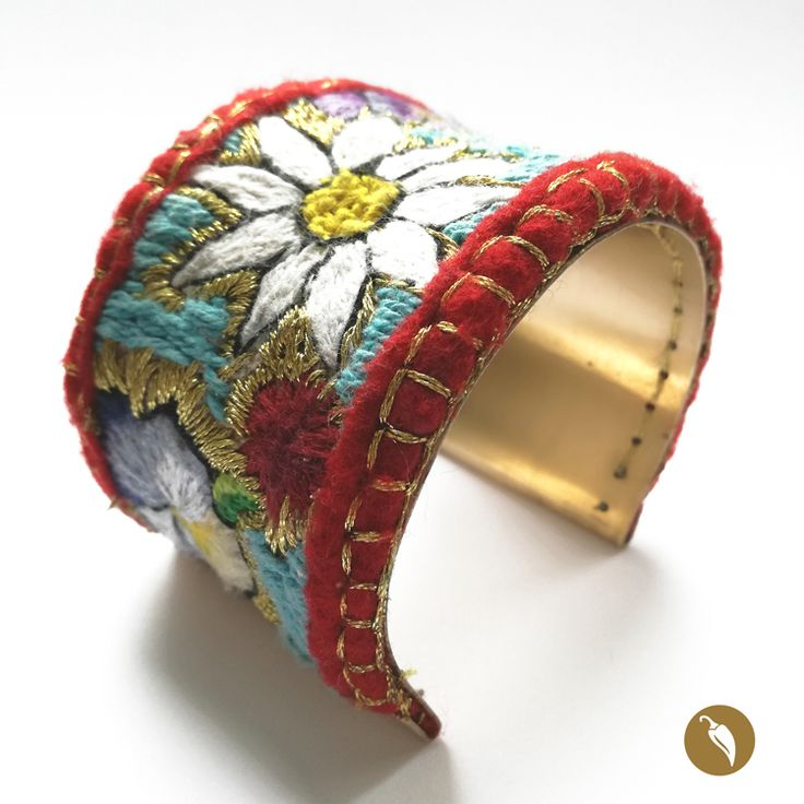 """Brazalete de bronce con una maravillosa cubierta bordada a mano. La joya está inspirada en la obra de Violeta Parra, específicamente en las formas representadas en las arpilleras que la artista presentó en el Louvre, en una exposición llamada """"Tapices de Violeta"""" el año 1964. Retomando el bordado como forma de expresión, Weichafe hace un homenaje a través de su joyería a Violeta Parra. Los colores utilizados, se intercalan con hebras doradas, de modo de realzar el bronce de la joya y…"""