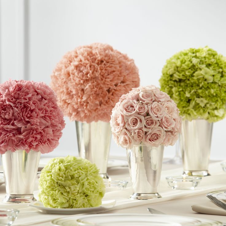 The FTD® Bridesmaid's Garden™ Centerpiece is a lovely way to bring bright, bold clusters of color to your reception. A collection of bouquets featuring a single type of flower, including peach carnations, pink carnations, pink spray roses, pistachio mini carnations, and green hydrangea are each set in small and medium silver julep cups to create a memorable display. #weddingflowers