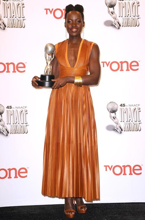 Lupita Nyong'o styled her burnt-orange Givenchy dress with matching accessories and a quirky new hairstyle.