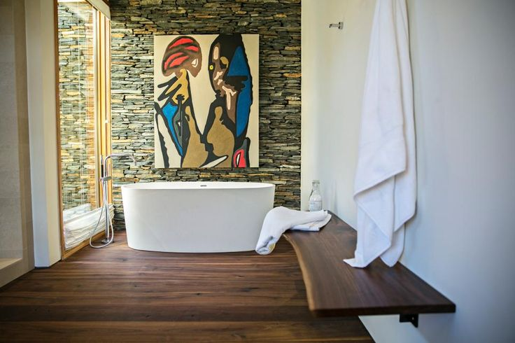 The freestanding bathtub in this luxurious bathroom offers a second-floor view into the trees, and the window treatment closes from the bottom up to create privacy without blocking the view. The warm wood floor has been treated numerous times with penetrating oils and sealers so it will hold its shape and color in wet conditions.