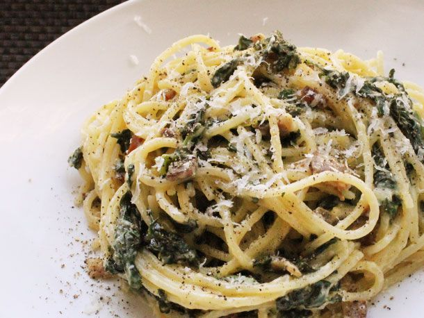 Skillet Spaghetti alla Carbonara with Kale (8 oz bacon, pancetta, or guanciale, cut into 1/2-inch pieces; 1 shallot, thinly sliced; 3 cups curly kale, chopped; Kosher salt and freshly ground black pepper; 3 ½ cups chicken stock or broth; 1 pound spaghetti; 4 eggs; 1 cup freshly grated Parmigiano-Reggiano)