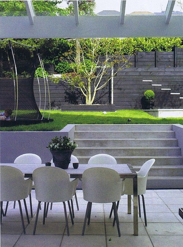 Concrete pavers, plaster block retained walls, black stained timber walls (and yes that's a sunken trampoline).  Designed by Rach Matthews, Photo courtesy of NZ House & Garden.  Designed by Rach Matthews, HEDGE Garden Design & Nursery