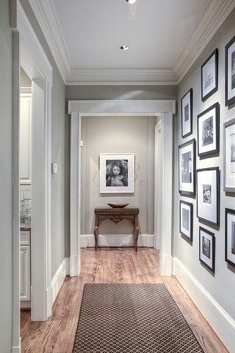 Love the pale gray with the white trim and black photo frames.