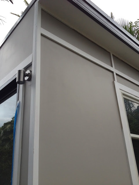 Dulux Calfskin for the cement sheeting and Dulux Natural White for the trim. The roofing is Colourbond Woodland Grey.