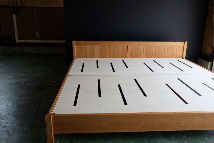 <ベッド> 本体:チェリー無垢(クリヤオイル仕上げ)  組み立て式   布団を2枚並べて使用するキングサイズのベッドです。   無垢の挽き板を嵌め込んだ框組のヘッドボードは高さ55cm。布団を敷いた時の上面は床から32cm。大きなベッドではありますが、高さを抑えてヘッドボードもすっきりとした印象で、無垢の木の質感もたっぷりと感じることの出来る仕上がりです。   脚もゴツく見えない太さにしていますが、床板を支える部材の下にも脚が2本あり、全体でしっかりと荷重を支える作りにしています。