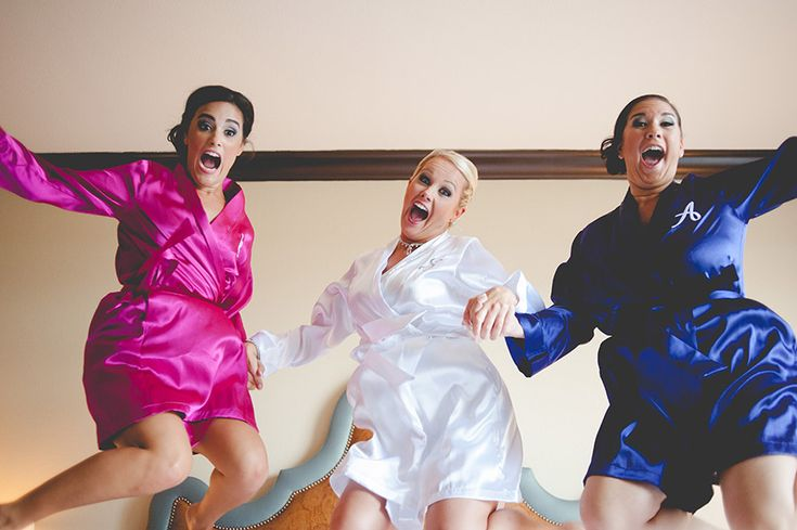 bridesmaids and bride in custom robes creatively jumping on the bed at their getting ready hotel in downtown austin