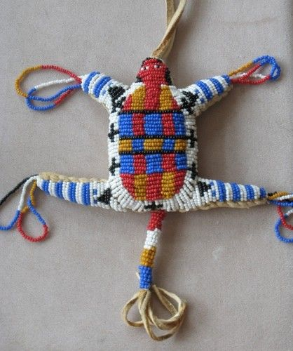 "Beaded Plains Indian amulet, traditionally made as a pouch for the umbilical cords of newborn babies.  Beaded buckskin part is 5 1/2"" L x  5"" W; Total size from very top and including beaded ""feet"" and buckskin tail:  12"" L x 8"" W. Excellent condiiton; light wear to buckskin back but don't know age of work. Bought with a group where others showed wear and use."