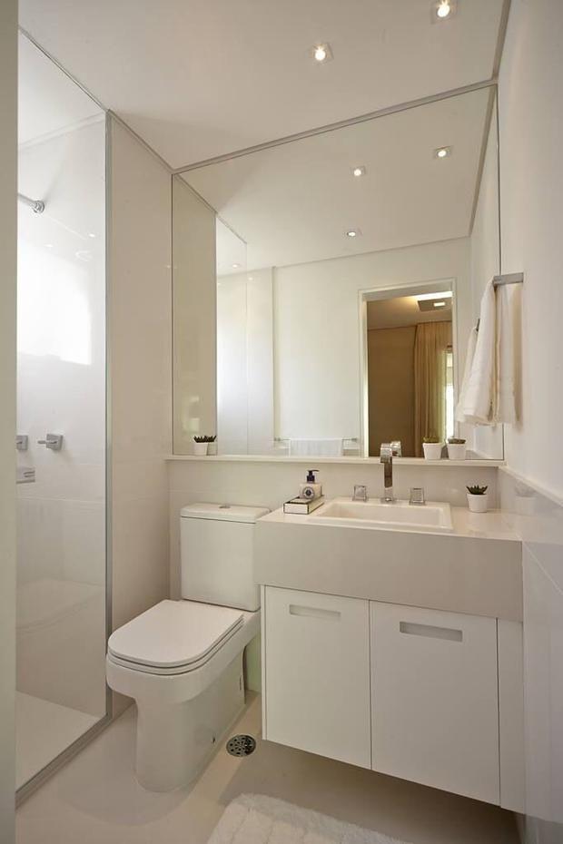 Banheiro pequeno com espelho e prateleira em pedra para apoio de decoração e produtos de higiene