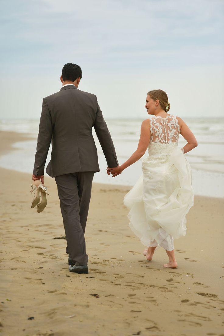 Bruid & bruidegom wandelen op het strand.