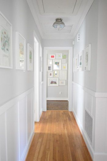 Benjamin Moore Moonshine is a bright panit colour for a dark hallway. Looks good with board and batten, wainscoting and wood flooring by Young House Love