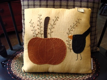"""Pumpkin Pillow @Country & Primitive: This is a really pretty pillow...and perfect to keep out all Autumn long. The wool/felt appliqued pillow features an orange pumpkin and black crow. (I can't find the """"exact"""" same pillow, but they have one for $21.00 that looks a little larger.)"""