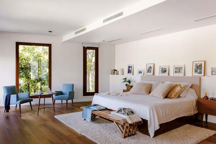 Dormitorio moderno con cama enchapada en madera y cabezal tapizado en lino. A los pies, banco 'V' de petiribí (Net Muebles) y carpetas color crema (Bazhars), a tono con la ropa de cama.
