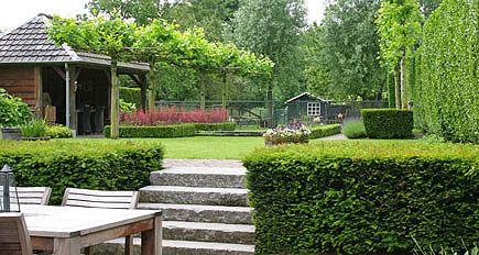 http://www.tuindesign-ten-horn.nl Tuinarchitect - tuinontwerp. Klassieke landelijke achtertuin met hoogteverschillen in Limburg. Een ruimtelijke tuin met een terras bij de woning en een onder de overkapping (tuinhuis) bij de vijver.