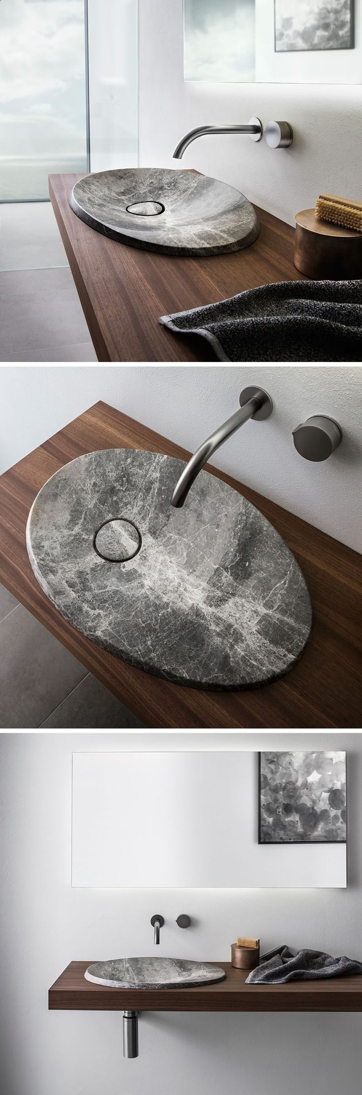 The bathroom also features a stainless steel sink and a full - This Modern Bathroom Sink Made From Natural Stone Sits On A Floating Wood Vanity And Has