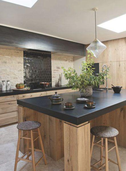Cuisine noire et bois - mur en pierres et carrelage noir brillant