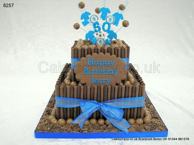 Square two tier stacked celebration cake covered in milk and plain chocolate rolls, maltesers and chocolate flakes. Tied together with a bright blue ribbon and topped with a wired explosive topper of your choice