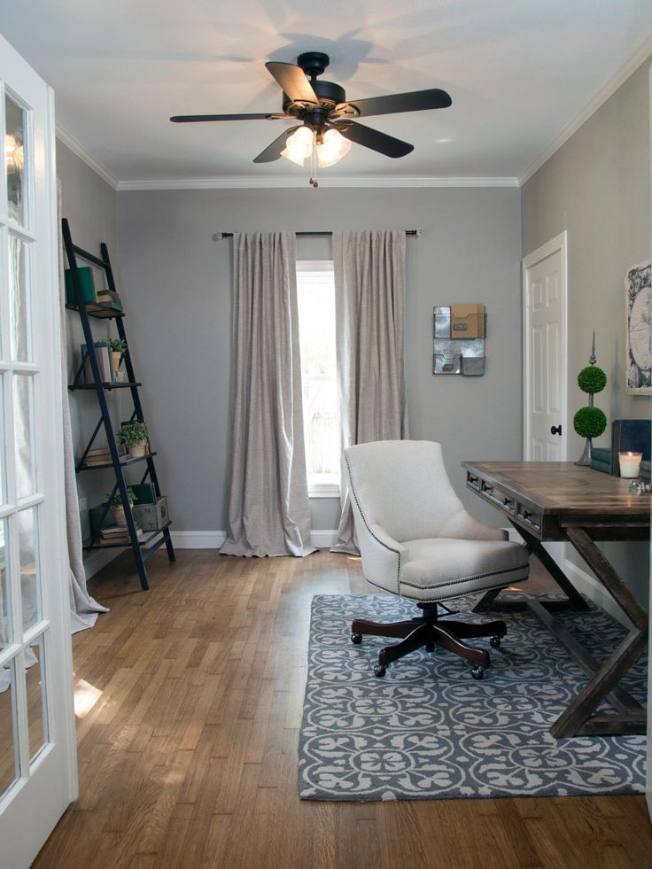 French doors were added to create an airy, yet private home office. The walls were painted a medium gray and bright linen window treatments create soft, natural mood. A new ceiling fan was installed, and the room is staged with a traditional desk and chair and a unique ladder bookshelf.