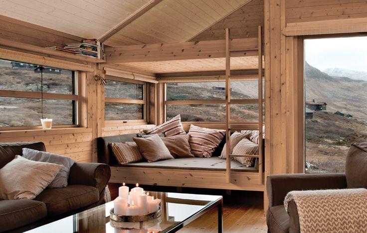 Moderne hytter med mye glass skaper åpne og lyse rom. Her beiset med Tyrilin Interiørbeis i farge 10 Kalkhvit i tak og farge 16 Morgenlød på veggen.