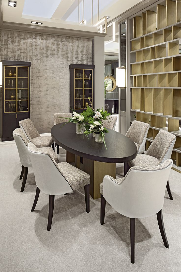 The large elliptic Tao table dominates the dining area. Comprising a wooden top and a base in bronze and wood, it is teamed with two-tone Musa chairs in dove-grey with contrast piping and mahogany legs.