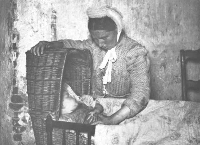 1900. Moeder en kind in een tenen wieg. Foto Henri Berssenbrugge omstreeks. (Coll. RHC Tilburg).