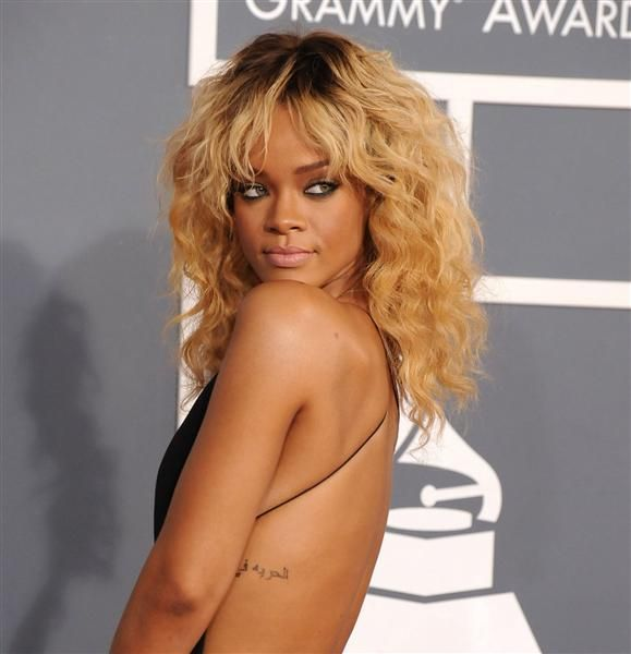"""Rihanna went Arabic for the tat on her left ribcage. It reportedly translates to """"freedom in God."""""""