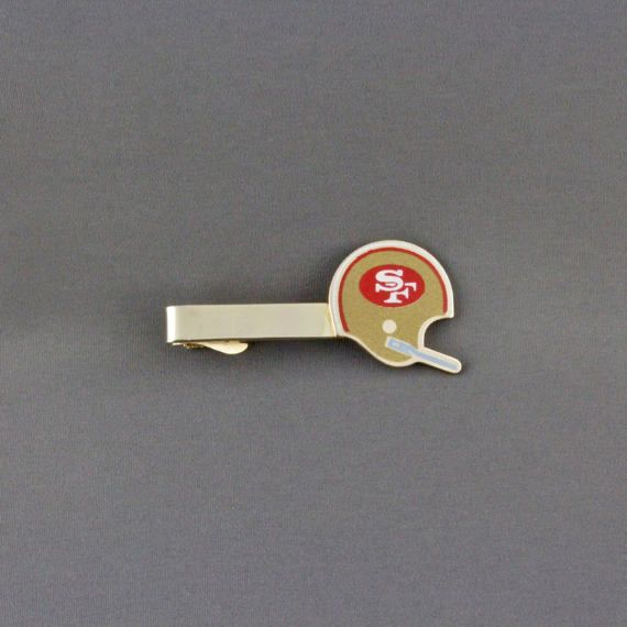 This is a great San Francisco 49ers football helmet tie clip. I believe that these are a replica of the helmet used by the NFL 49ers during the 1980s because of the single bar facemask. The gold tone tie bar is cutout in the shape of the helmet and have the trademark SF in white within a red oval. The helmet is gold with red and white stripes and a blue facemask. A great piece of memorabilia from a great football team.  I have the matching cufflinks for sale, Item ID# CL-494  A large size…