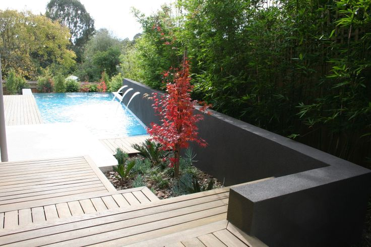 View into pool area with deck landing water feature wall and bamboo screen plantings. Balwyn display home. www.marktraversla.com