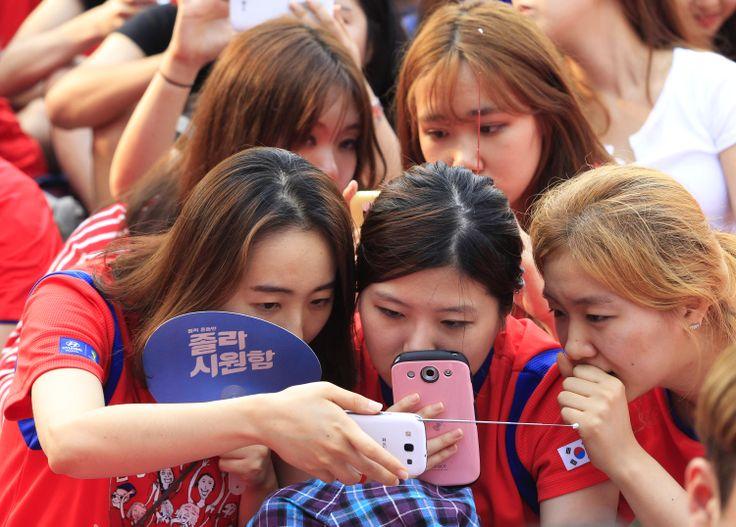 Gadis-gadis Korea Selatan melihat tim Korsel bertanding melawan Rusia dari ponsel pintar mereka karena layar lebar untuk nonton bersama (nobar) mati akibat kerusakan teknis di Seoul.