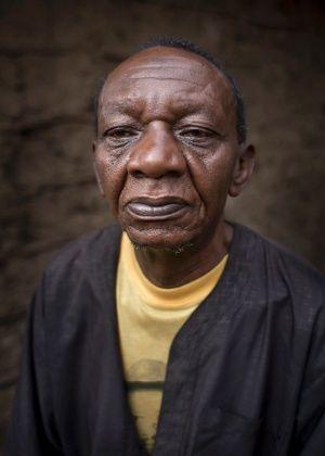 """J. A. A., 65, morador da favela de Kibera em Nairóbi, no Quênia. """"Estamos esperando os títulos de propriedade da nossa terra e, o principal problema é como vamos deixar uma casa para nossos filhos e netos. ...  Minha saúde é um problema, eu não tenho força, do jeito que eu estou ficando velho. Existem diferentes tipos de idosos; quem tem dinheiro pode ser levado para casa de repouso, mas para aqueles que não têm recursos, não há para onde ir"""".  Fotografia:  Ben Curtis / AP."""