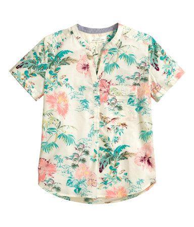 Blusa de algodón con cuello de pico y botones en la parte superior. Un bolsillo superior con solapa y botón y mangas cortas con dobladillo vuelto cosido.