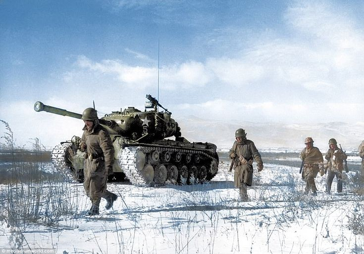 US troops trek through the snow during the Korean War. The soldiers are wearing hoods and ...