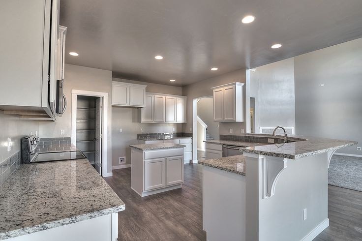 Huge kitchen with Merillat - Spring Valley, Maple, Cotton Cabinets, wood corbels under the raised breakfast bar, Woodland Maple wood laminate flooring, and Ashen White slab granite with an eased edge.