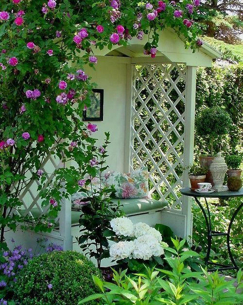Romantic covered garden bench surrounded by dark pink climbing roses and some green plants in containers and a pretty white ginger jar with a lid.
