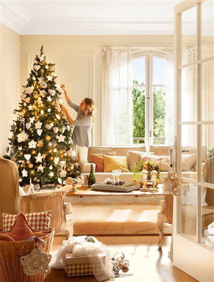 Mujer decorando el árbol de Navidad en salón: