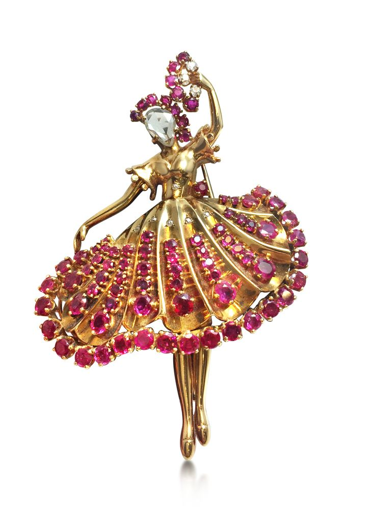 A retro ruby and diamond ballerina brooch, circa 1950. Designed as a ballerina with a rose-cut diamond face with skirt, headpiece and fan set in circular rubies, mounted in 18K yellow gold.