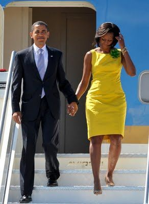 First Lady Michelle Obama arrives in Rome, Italy for the G8 Summit with President Barack Obama wearing this yellow Jason Wu sheath with bright green flower brooch.