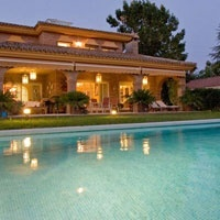 Two-storey villa in one of the main streets of the urbanization Santa Clara, Seville, Spain, with a bright living room with large windows overlooking the garden and pool area.