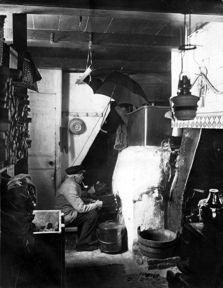 Vader Peterse, een der laatste water- en vuurverkopers te Amsterdam uit de Suikerbakkerssteeg. Onder een paraplu en een pijp rokend zit hij ...