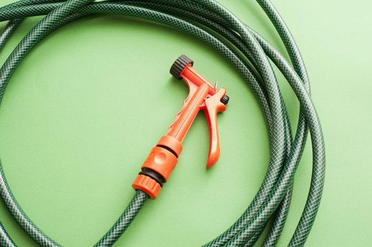 Orange plastic garden sprayer attached to the end of a neatly coiled green hosepipe on a green background - free stock photo from www.freeimages.co.uk