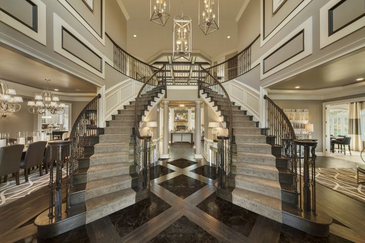 Boasting a two-story foyer with stunning double turned staircases, the visitor's first impression of the Dutchess model is one of luxury and extravagance – from the floor to the ceiling. | Image courtesy of Possibilities for Design and Toll Brothers featuring Piedmont lanterns
