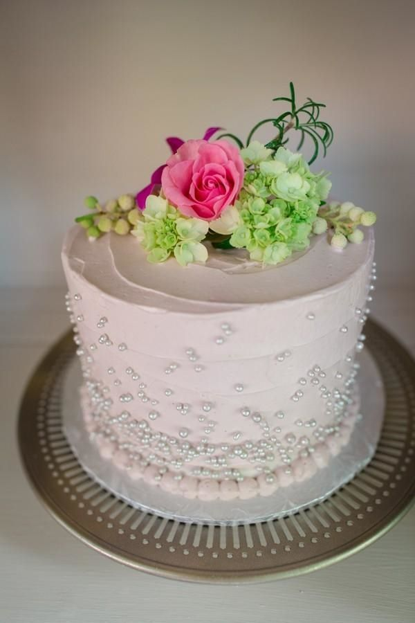 Light pink wedding cake with pearls, topped with pink and green flowers