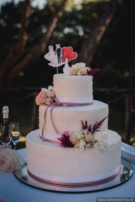 Classica torta nuziale a tre piani con nastrini di raso rosa e fiori