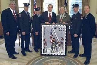 """Firefighters and photographer are reunited at the stamp unveiling on March 11, 2002, six months after the Trade Center attack. Standing (from left) are Postmaster General Jack Potter, Firefighters William """"Billy"""" Eisengrein and George Johnson, President George W. Bush, US Rep. Gary Ackerman (D-N.Y.), Firefighter Dan McWilliams, and Thomas E. Franklin. (White House photo)"""
