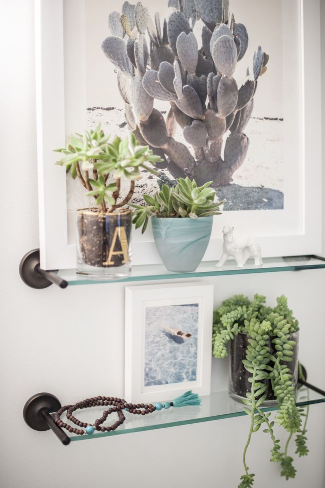 a small stylized glass shelving unit positioned low on a crisp white wall helps