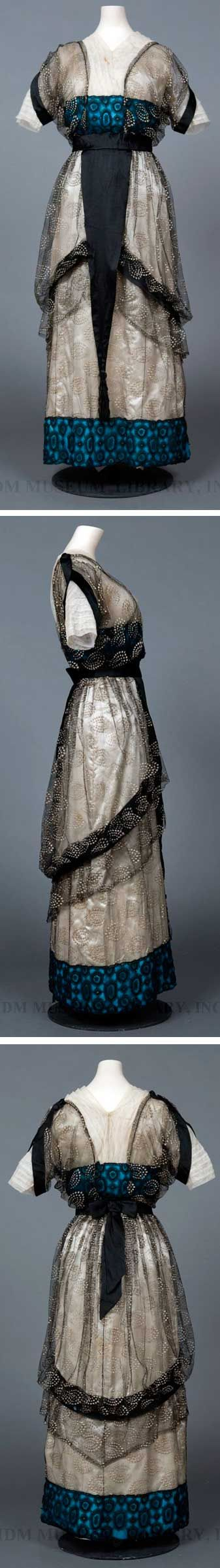 Evening dress, ca. 1912, in the style of Paul Poiret. Draped surplice bodice with V-shaped yoke and elbow-length sleeves. Black chiffon tunic over cream-colored silk, both with white polka dots in concentric circles. Skirt is banded by turquoise chiffon with an overlay of black lace. Dress hits at instep, which was considered more youthful than the traditional floor length. It needed matching slippers. FIDM