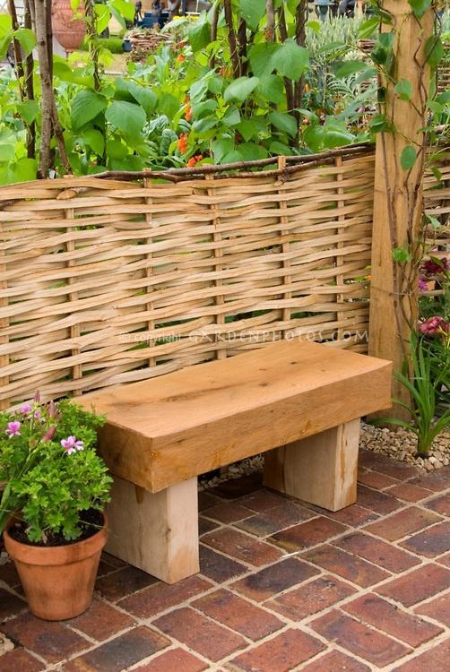 Wooden garden bench against willow woven fence in garden